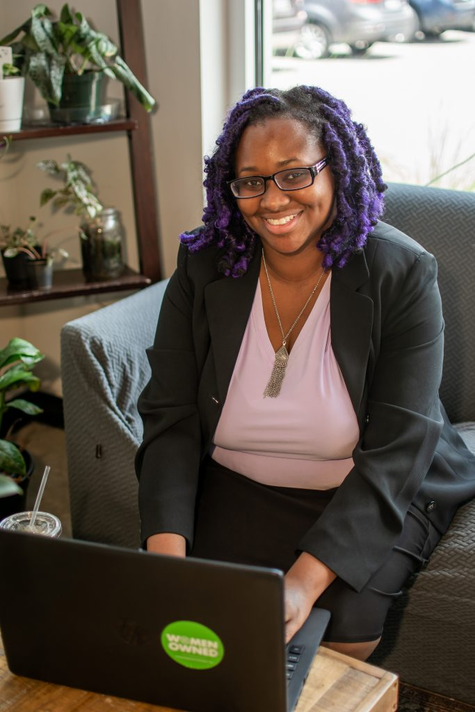 Adriana is a brown skinned woman sitting on a chair with a lavendar shirt, purple twists, Black blazer, and black skirt. She is seen with her hands on her laptop and smiling to the camera.