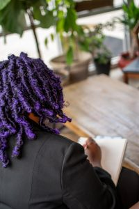 Pictured is the back of Adriana's head. She has purple twist and is writing in a notebook